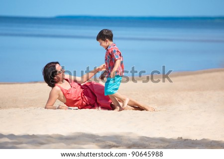Mother and her little son playing on the beach