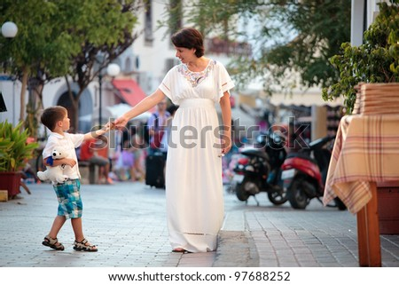 Mother and her little son walking in city