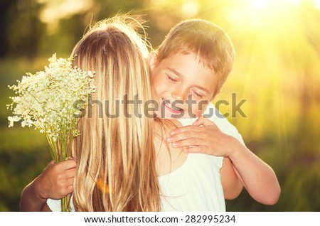 Mother and her little son with bouquet of flowers outdoors, Happy family mom and kid kissing and hugging. Mother\'s day gift.