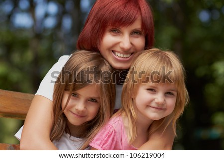 Mother and her pretty little daughters posing outdoors in a bright sunny day.