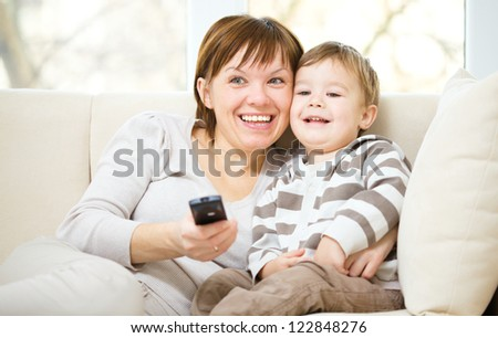 Mother and her son are watching tv while sitting on a couch - stock photo