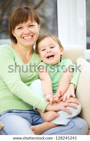 Mother and her son are watching tv while sitting on a couch