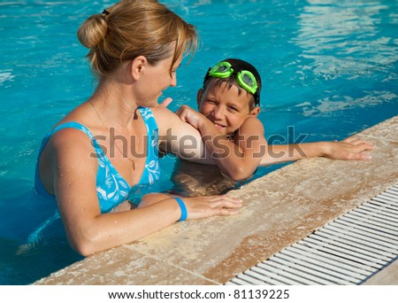 Mother and her son in the swimming pool. Swimming lessons.
