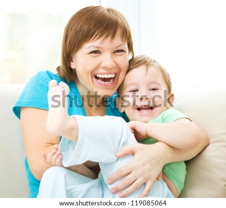 Mother and her son is having fun while sitting on a couch