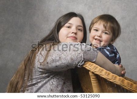 Mother and her son look at camera smiling