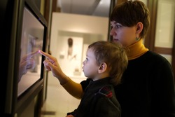 Mother and her son using touch screen in a museum