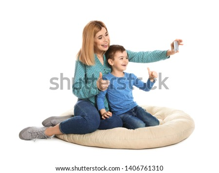 Mother and her son using video chat on smartphone, white background