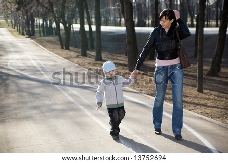 Mother and her son walking in a park #13752694