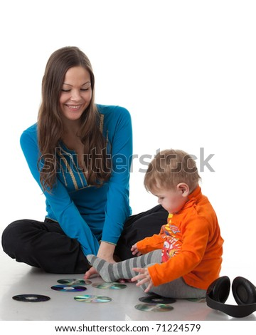 Mother and  her sweet  baby  with earphones and CD  on a white background. Happy family.