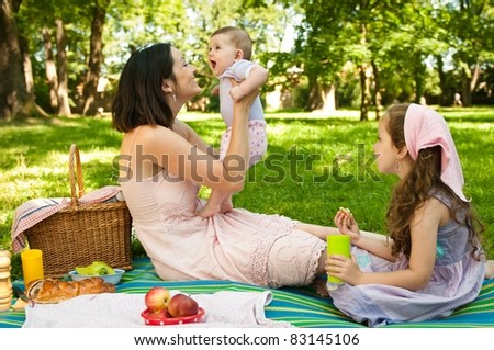 Mother and her two children having picnic in park, playing with baby