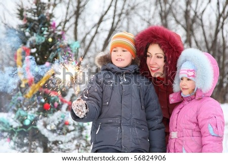 mother and her two children is standing near christmas tree and looking at bengal light in boy's hand. christmas tree in out of focus. - stock photo