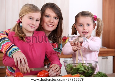 mother and her two girls making a salad
