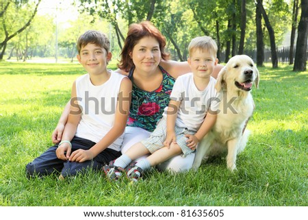 Mother and her two sons in the park with a golden retriever dog