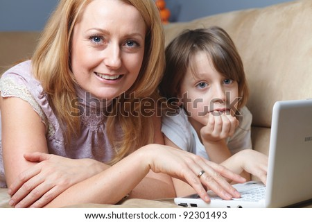 Mother and her young son lying on the sofa and work on small netbook computer