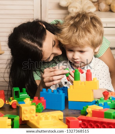 Mother and kid boy playing colorful block toys at home on light wooden background #1327368515