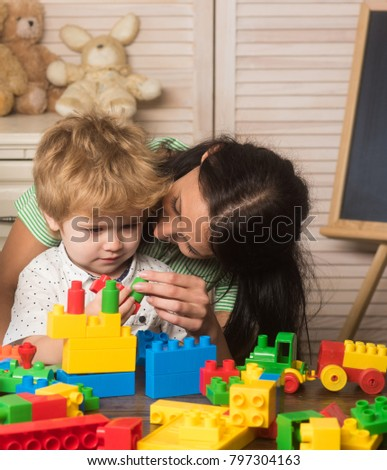 Mother and kid boy playing colorful block toys at home on light wooden background #797304163
