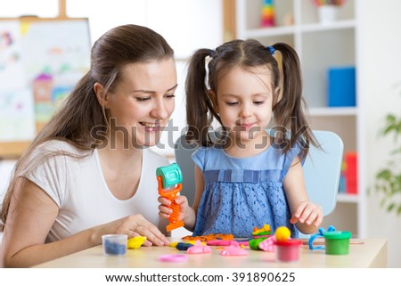 Mother and kid daughter at home molded from clay and play together. Concept of preschool or home education.