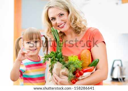 mother and kid holding a shopping bag full of vegetables  on kitchen