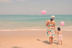 Mother and  kid on the beach with pink balloons vintage , happy mothers day vintage retro style