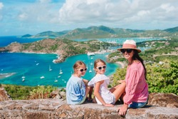 Mother and kids at English Harbour at Antigua. View of paradise bay at tropical island in the Caribbean Sea. Family vacation.