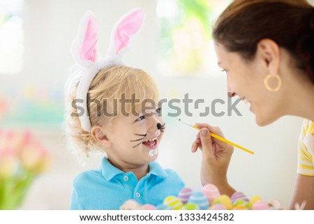 Mother and kids color Easter eggs. Face painting for little child. Little boy with bunny ears and mom dye eggs. Easter egg hunt. Family celebration and home decoration for spring holiday.