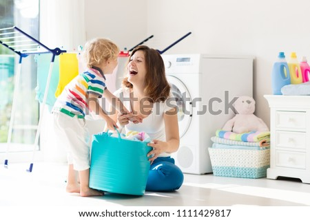 Mother and kids in laundry room with washing machine or tumble dryer. Family chores. Modern household devices and washing detergent in white sunny home. Clean washed clothes on drying rack.