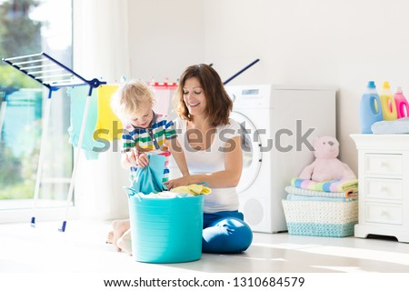 Mother and kids in laundry room with washing machine or tumble dryer. Family chores. Modern household devices and washing detergent in white sunny home. Clean washed clothes on drying rack.  #1310684579