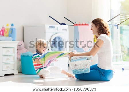 Mother and kids in laundry room with washing machine or tumble dryer. Family chores. Modern household devices and washing detergent in white sunny home. Clean washed clothes on drying rack.  #1358998373