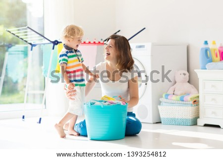 Mother and kids in laundry room with washing machine or tumble dryer. Family chores. Modern household devices and washing detergent in white sunny home. Clean washed clothes on drying rack.  #1393254812