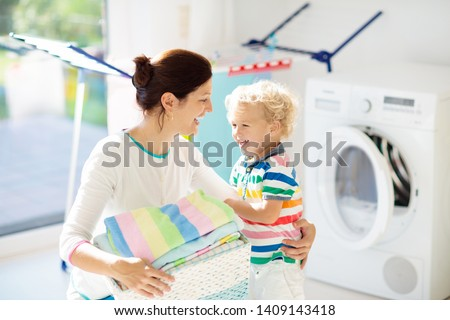 Mother and kids in laundry room with washing machine or tumble dryer. Family chores. Modern household devices and washing detergent in white sunny home. Clean washed clothes on drying rack.  #1409143418