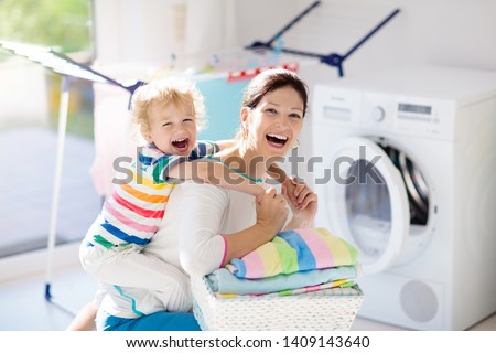 Mother and kids in laundry room with washing machine or tumble dryer. Family chores. Modern household devices and washing detergent in white sunny home. Clean washed clothes on drying rack.  #1409143640