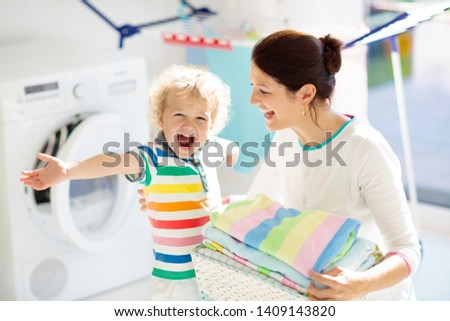 Mother and kids in laundry room with washing machine or tumble dryer. Family chores. Modern household devices and washing detergent in white sunny home. Clean washed clothes on drying rack.  #1409143820