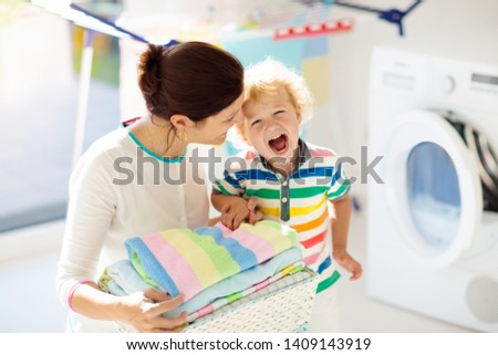 Mother and kids in laundry room with washing machine or tumble dryer. Family chores. Modern household devices and washing detergent in white sunny home. Clean washed clothes on drying rack.  #1409143919