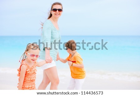 Mother and kids on Caribbean vacation walking along the beach