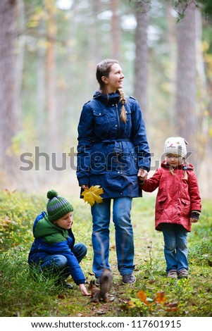 Mother and kids outdoors at beautiful autumn park