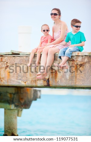Mother and kids sitting on a wooden dock