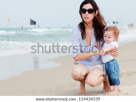 Mother and little baby having fun on the beach