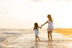 Mother and little daughter are having fun on the beach.