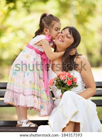 Mother and little daughter embracing outdoors.