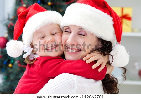 Mother and little daughter in santa suit holding in Christmas day