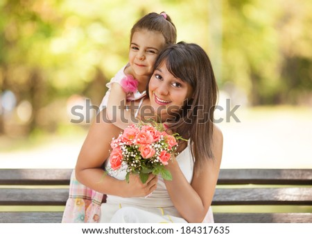 Mother and little daughter portrait in a park.