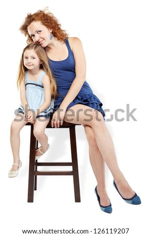 Mother and little daughter sit on brown wooden stool
