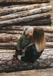 Mother and little daughter sitting in a wood trunks pile and kissing.