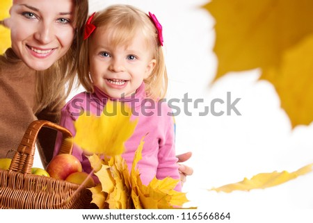 Mother and little daughter with basket and falling yellow leaves