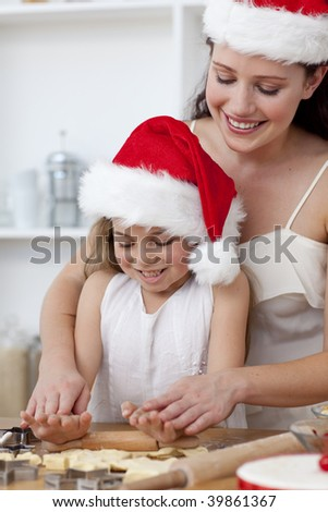 Mother and little girl baking Christmas cakes in the kitchen - stock photo