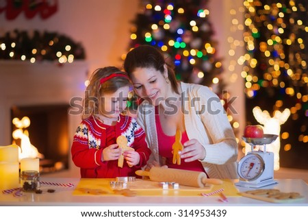 Mother and little girl baking Christmas pastry. Children bake gingerbread. Toddler child preparing cookie for family dinner on Xmas eve. Decorated kitchen or dining room with fireplace, tree, candles.