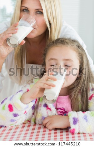 Mother and little girl drinking milk at the kitchen at breakfast