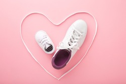 Mother and little kid shoes. Heart created from white shoelaces. Light pink floor background. Pastel color. Love sport together concept. Closeup.