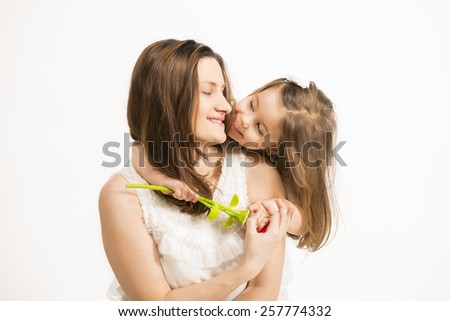 Mother and little lovely daughter. Beautiful little girl embracing her mother on white background. Happy family concept. Mothers day. #257774332