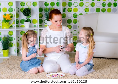 Mother and little sisters making a necklace from wooden beads and a string